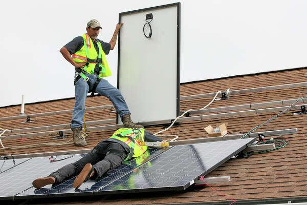 Solar installers Tony Medellin (top) and Logan Roerig install solar panels under a new Simply Solar program on the home of Myra Garcia on Dec. 10.