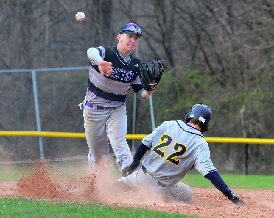Westhill shortstop Johnny Spoto turns a double play as Weston Dan Covino slides into second base in the fourth inning of  a boys varsity baseball game at Westhill High School on April 6, 2016. Westhill defeated Weston 3-1. Photo: Matthew Brown / Hearst Connecticut Media / Stamford Advocate