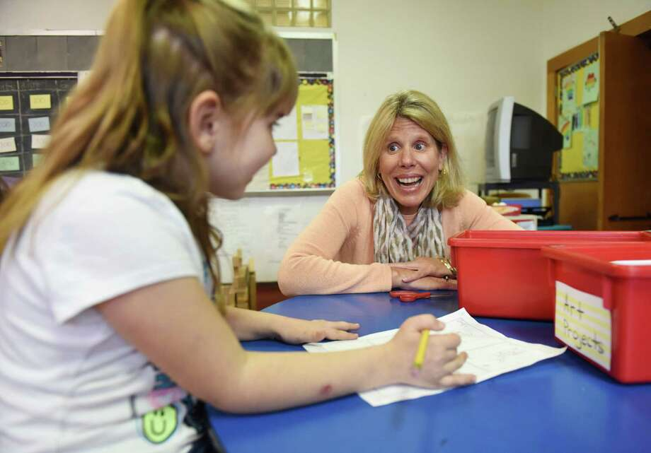 Greenwich volunteer Monica Collins helps Dominika Jakab, 7, with work at the after-school care program at the YMCA in Greenwich, Conn. Wednesday, April 6, 2016. YMCA after school care volunteers work in one-hour shifts once a week to watch over the children and lend a helping hand with homework. Photo: Tyler Sizemore / Hearst Connecticut Media / Greenwich Time