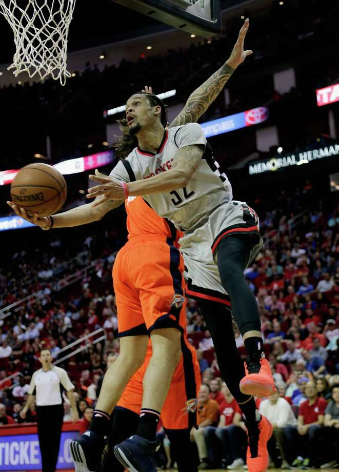 Houston Rockets' K.J. McDaniels (32) drives around Oklahoma City Thunder's Steven Adams (12) for a reverse layup during a basketball game Sunday, April 3, 2016, in Houston. Houston won 118-110. (AP Photo/Bob Levey) Photo: Bob Levey, FRE / FR156786 AP