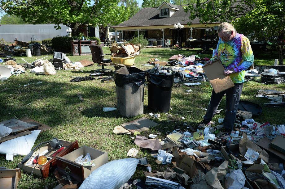 Virginia Hyatt picks up debris at her sisters Deweyville home on Monday.  Photo taken Monday, April 04, 2016 Guiseppe Barranco/The Enterprise Photo: Guiseppe Barranco, Photo Editor