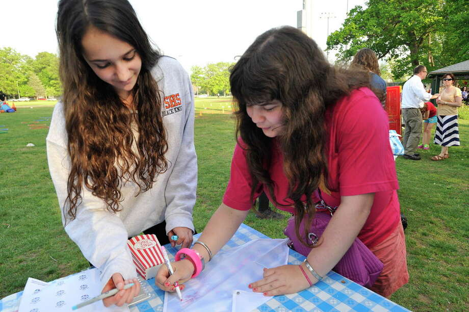Volunteer Marissa Young, left, helps Hilary Greenwald decorate a kite during the Friendship Circle's end-of-year barbecue at Scalzi Park in Stamford, Conn., on Tuesday, May 19, 2015. Friendship Circle is a non-profit organization that pairs volunteers with people with special needs. The organization works with volunteers help to offer a full range of social and Judaic programs. Photo: Jason Rearick / Jason Rearick / Stamford Advocate