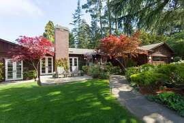 A winding walkway leads to the entrance of 9535 Skyline Blvd., a three-bedroom midcentury on a quarter-acre lot in Montclair.�