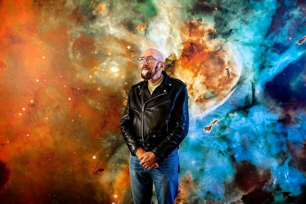 """PASADENA - CA - NOVEMBER 11, 2014 - Astrophysicist Kip Thorne photograph in front of a stellar mural at California Institute of Technology, November 11, 2014, in the Cahill Center for Astronomy and Astrophysics where Thorne has his office. Thorne, whose research into black holes and worm holes helped form the basis for the sci-fi movie """"Interstellar."""" (Photo by Ricardo DeAratanha/Los Angeles Times via Getty Images)"""