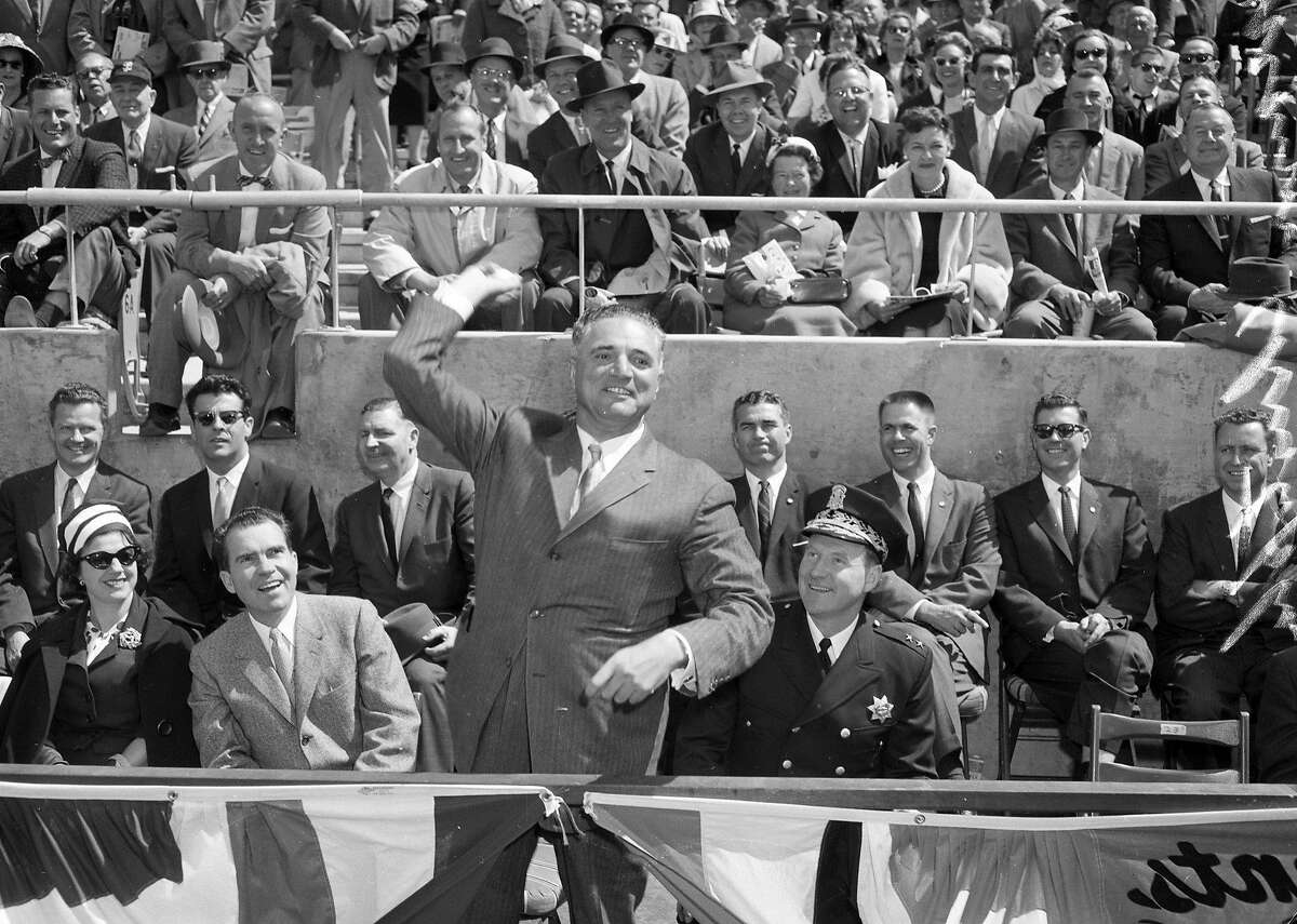 On April 12, 1960, Mayor George Christopher throws a ball as Richard Nixon watches before opening day at Candlestick Park.