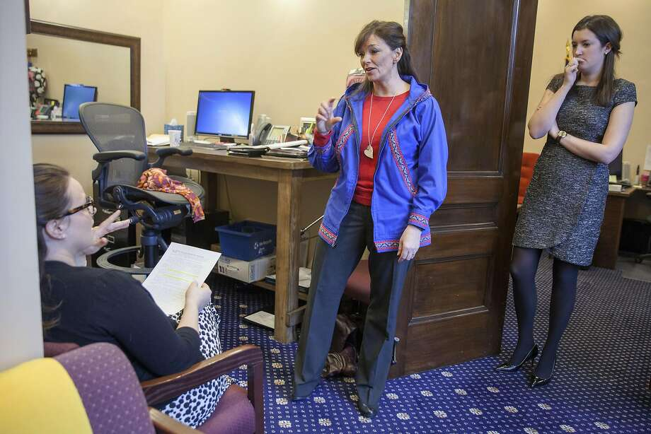 In this Friday, March 25, 2016 photo, House Majority Leader Rep. Charisse Millett, R-Anchorage, talks with her staff while donning her kuspuk for a floor session, in Juneau, Alaska. Millett and others in the Alaska Legislature regularly observe an informal Friday tradition where they wear their own versions of the traditional Alaska Native garment. For more than a decade, the tradition has grown to include lawmakers and their staff and even Senate pages who are fitted and gifted with a kuspuk to be worn in lieu of their distinctive blazers on Fridays. (AP Photo/Rashah McChesney) Photo: Rashah McChesney, AP