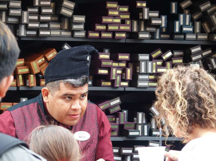 A clerk helps Harry Potter fans pick out the correct wand.
