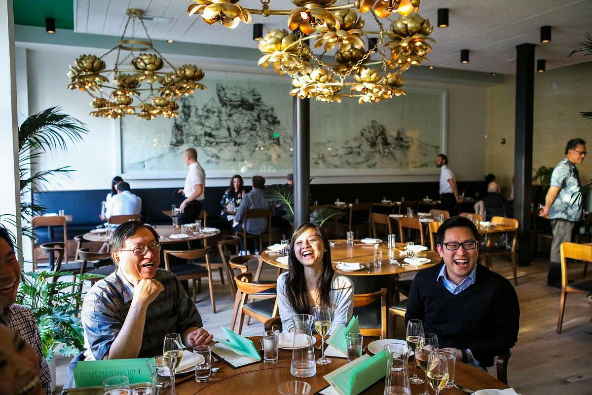 (l-r) Thomas Wong, Erika Lam and Brian Ko share a laugh as they dine at the friends and family preview of Mister Jiu's restaurant in San Francisco, California, on Wednesday, April 6, 2016.