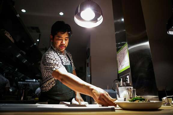 Chef Brandon Jew, sets down the smokes hood tofu, as it is ready to be served, at the soft opening of his restaurant Mister Jiu's, in San Francisco, California, on Wednesday, April 6, 2016.