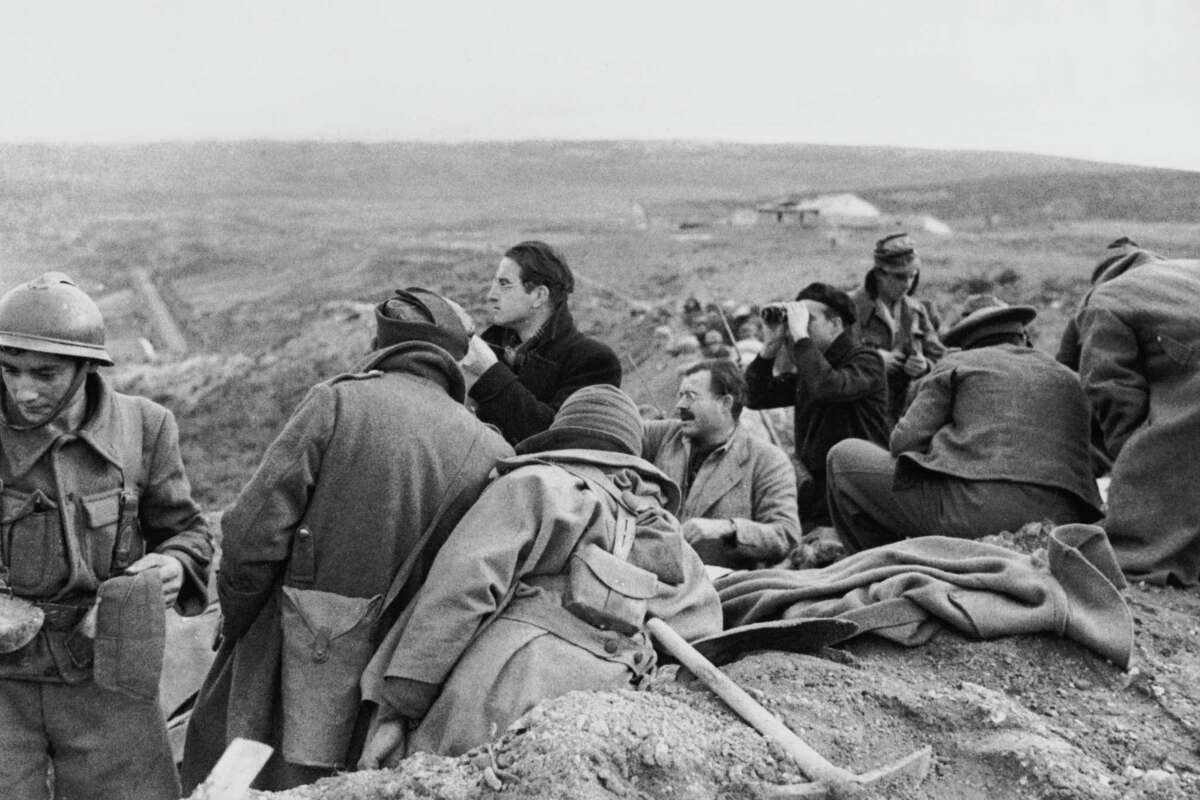 Ernest Hemingway (center right) in a trench with fellow war correspondents during the Spanish Civil War, circa 1937.