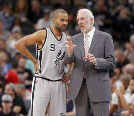 San Antonio Spurs head coach Gregg Popovich, right, talks with guard Tony Parker, left, during the third quarter of an NBA basketball game, Saturday, April 2, 2016, in San Antonio. (AP Photo/Michael Thomas)