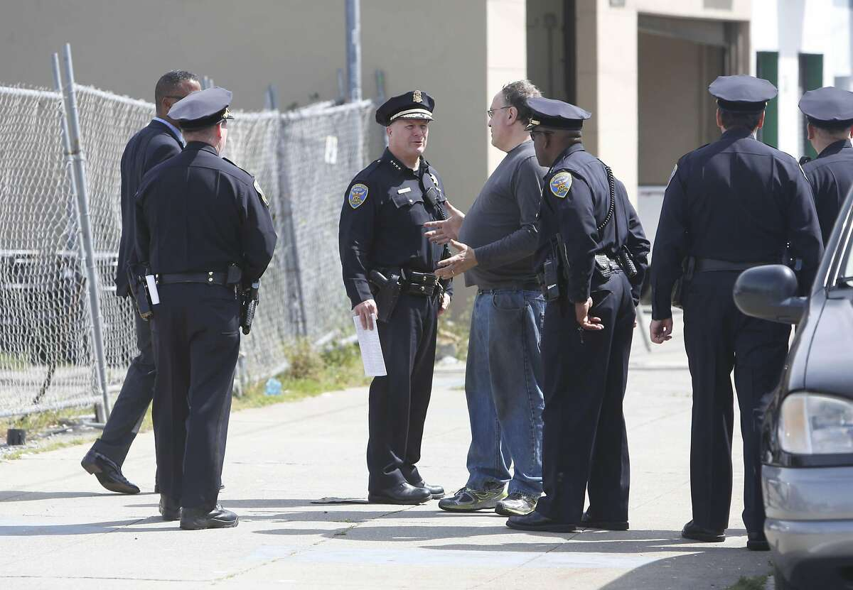 Police Chief Greg Suhr (center left) talks with Gary Siegel (center right), who heard gunshots from his auto repair business after Suhr gave an update on an officer-involved-shooting on Thursday, April 7, 2016 in San Francisco.
