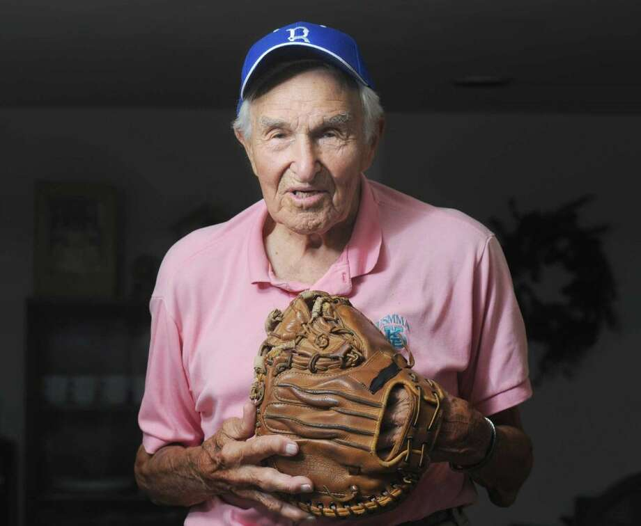 Mike Sandlock poses with his catcher's glove during a visit at his home in Greenwich in 2012. Sandlock died this week at age 100. Photo: Bob Luckey Jr. / Bob Luckey Jr. / Greenwich Time