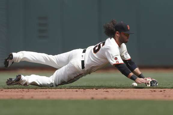 San Francisco Giants shortstop Brandon Crawford stops a ball but is unable to get  the out on a ground ball hit by the Los Angeles Dodgers' Joc Pederson during the second inning of the home opening day game on Thursday, April 7, 2016 in San Francisco, Calif.