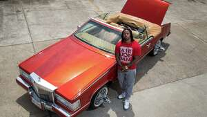 Chris Lockett poses for a portrait with his custom Cadillac Eldorado, in Houston. Lockett has worked on the car for three years, and he will drive it in this year's Houston Art Car Parade.