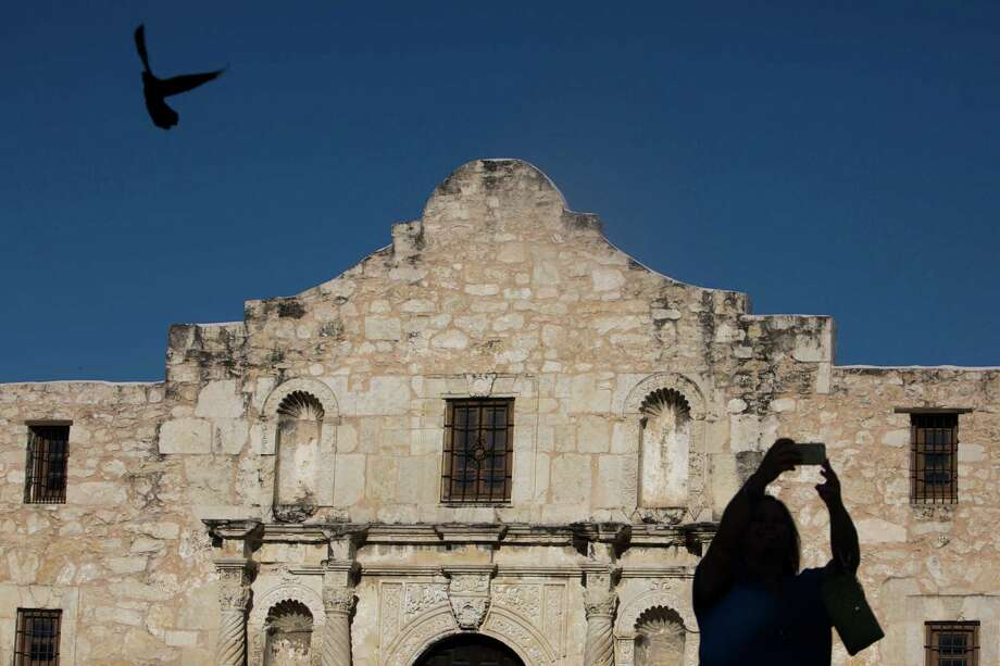 A tourist takes a selfie at the Alamo last year. A draft master plan for the shrine is in the works. Photo: Carolyn Van Houten /San Antonio Express-News / 2015 San Antonio Express-News