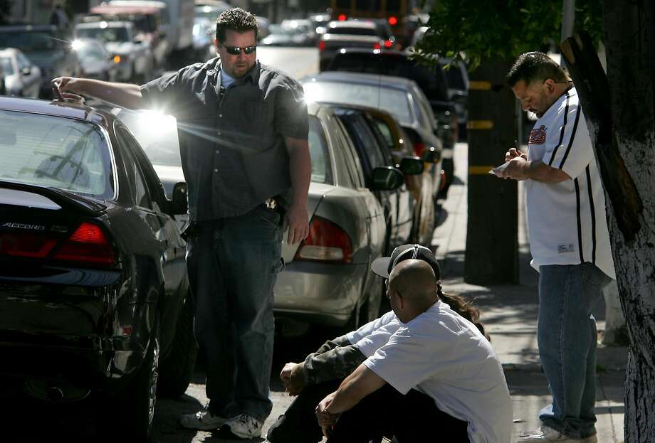 Officers Dion McDonnell (left) and Henry Espinoza ask two men about items found in their car. Photo: Brant Ward, SFC