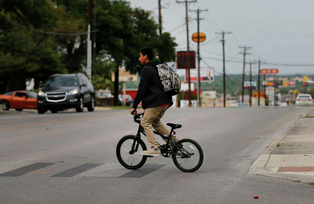 A young man rides his bicycle while crossing the intersection of Mt. Tipton and West Avenue where earlier in the day a 12-year-old girl died when a vehicle struck her as she attempted to cross West Avenue on her way to Eisenhower Middle School on Thursday, Apr. 7, 2016. According to San Antonio Police, the girl was crossing against the pedestrian signal when the incident occurred.