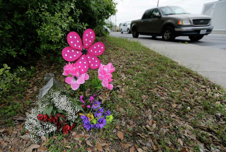 A small arrangement of flowers is seen on the ground near the intersection of Mt. Tipton and West Avenue for a 12-year-old girl who died when a vehicle struck her as she attempted to cross West Avenue on her way to Eisenhower Middle School on Thursday, Apr. 7, 2016. According to San Antonio Police, the girl was crossing against the pedestrian signal when the incident occurred. (Kin Man Hui/San Antonio Express-News) Photo: Kin Man Hui, Staff / San Antonio Express-News / ©2016 San Antonio Express-News