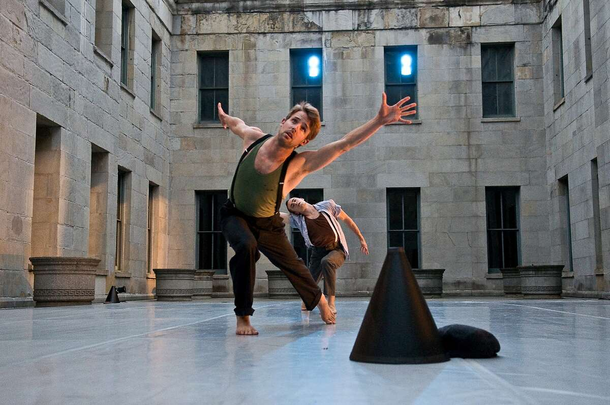 """Alexander Zendzain (front) and Andrew Ward dance in the courtyard of the Old Mint, the site of Joe Goode Performance Group�s """"Traveling Light."""" JGPG provided blankets to keep the audience cozy on the chilly SF summer evenings. Photo by Lynne Fried"""