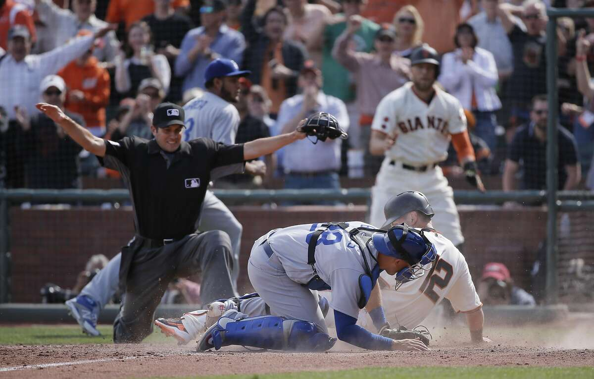 Giants' Joe Panik, 12 beats the tag by Dodgers' catcher Austin Barnes, 28 on a Buster Posey, 28 double in the sixth inning to give the Giants a 7-4 lead, as the San Francisco Giants take on the Los Angeles Dodgers during their home opener of the 2016 MLB season, at AT&T Park in San Francisco, California on Thurs. April 7, 2016.