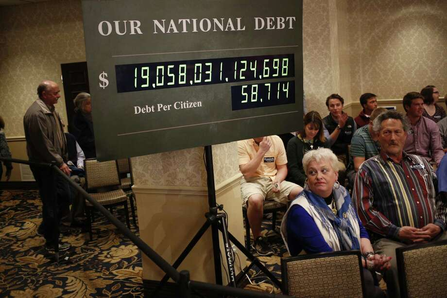 Attendees sit beneath a rendition of the U.S. national debt clock at an event for John Kasich, governor of Ohio and 2016 Republican presidential candidate, in Madison, Wis. Photo: Luke Sharrett, Stringer / © 2016 Bloomberg Finance LP