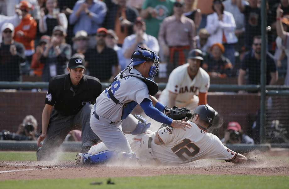 Giants' Joe Panik, 12 beats the tag by Dodgers' catcher Austin Barnes, 28  on a Buster Posey, 28 double in the sixth inning to give the Giants a 7-4 lead, as the San Francisco Giants take on the Los Angeles Dodgers during their home opener of the 2016 MLB season, at AT&T Park in San Francisco, California on Thurs. April 7, 2016. Photo: Michael Macor, The Chronicle