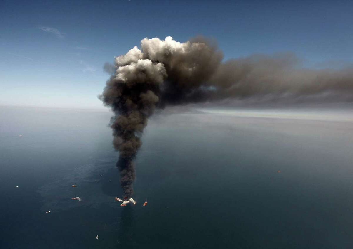 In this Wednesday, April 21, 2010 file photo, oil can be seen in the Gulf of Mexico, more than 50 miles southeast of Venice on Louisiana's tip, as a large plume of smoke rises from fires on BP's Deepwater Horizon offshore oil rig. An April 20, 2010 explosion at the offshore platform killed 11 men, and the subsequent leak released an estimated 172 million gallons of petroleum into the gulf. (AP Photo/Gerald Herbert, File)