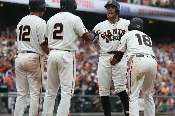 San Francisco Giants' Hunter Pence is congratulated by Joe Panik (12), Denard Span (2) and Angel Pagan (16) after all three scored on a grand slam by Pence during the eighth inning of the home opening day game against the Los Angeles Dodgers on Thursday, April 7, 2016 in San Francisco, Calif.