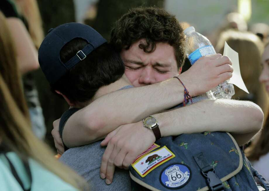 Texas students embrace during a gathering for fellow student Haruka Weiser on campus, Thursday, April 7, 2016, in Austin, Texas. Weiser, 18, a first-year dance student from Oregon, was last seen leaving a university drama building Sunday night. Her body was discovered in a creek in the heart of the university's Austin campus on Tuesday. (AP Photo/Eric Gay)