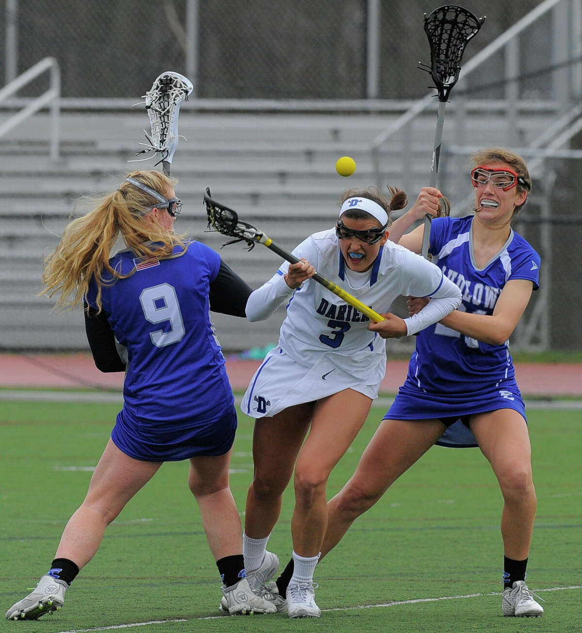 Darien Emma Lesko fights to recover a loose ball between Fairfield Ludlowe Paige Wilkman (9) and Amanda Schramm (21) in the first half of a FCIAC girls lacrosse game at Darien High School on April 7, 2016. Darien defeated Fairfield Ludlowe 19-6.