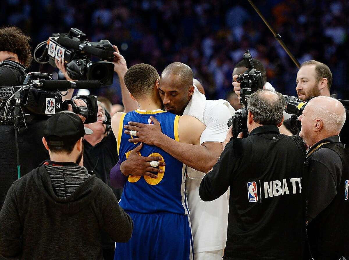 Kobe Bryant of the Los Angeles Lakers hugs Stephen Curry #30 of the Golden State Warriors at the end of the basketball game at Staples Center March 6, 2016, in Los Angeles.