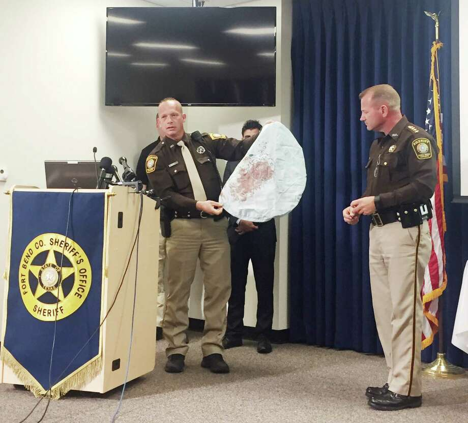 Deputy Danny Beckworth, who investigated the site after a minor accident, shows part of the air bag that killed Houston teen Huma Hanif last week. / Houston Chronicle