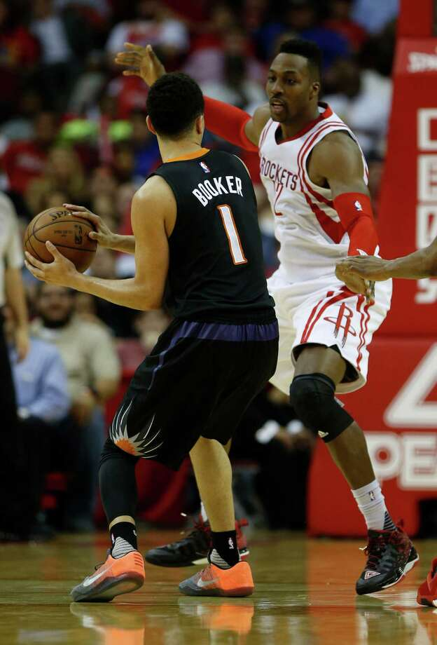 Houston Rockets center Dwight Howard (12) defends against Phoenix Suns guard Devin Booker (1) during the second half of an NBA basketball game at Toyota Center, Thursday, April 7, 2016, in Houston.  Rockets lost to Phoenix 124-115. Photo: Karen Warren, Houston Chronicle / © 2016  Houston Chronicle