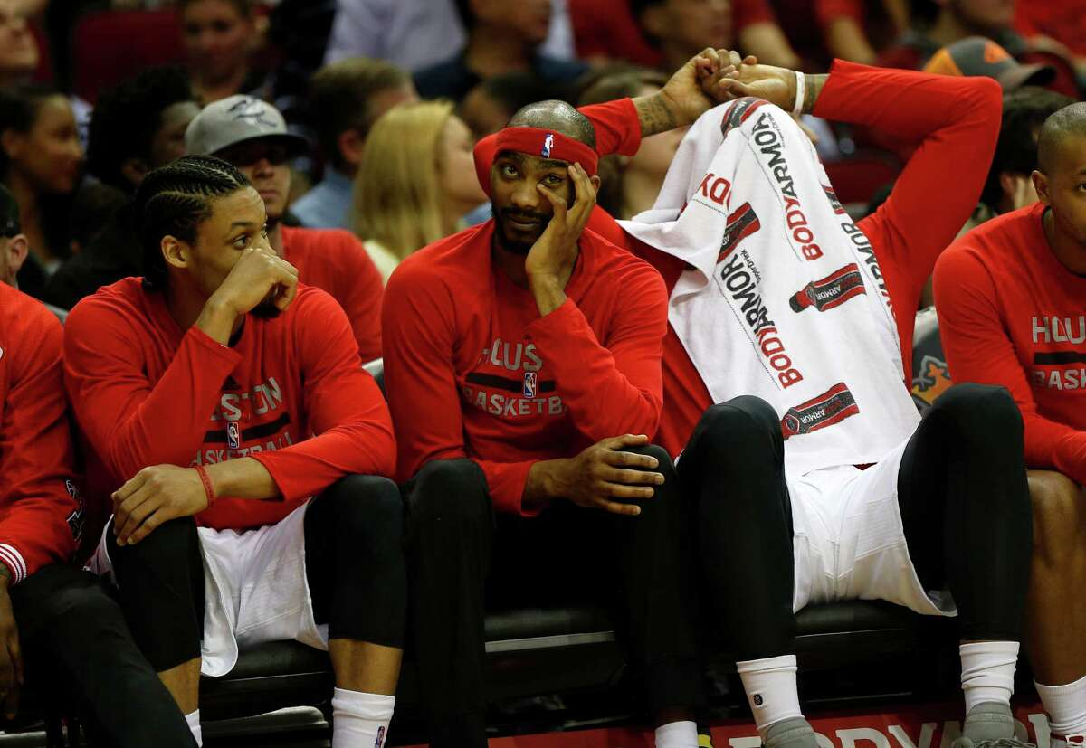 Houston Rockets guard K.J. McDaniels, Corey Brewer and Josh Smith, covering his head, react on the bench in the final minute during the second half of an NBA basketball game at Toyota Center, Thursday, April 7, 2016, in Houston. Rockets lost to Phoenix 124-115.