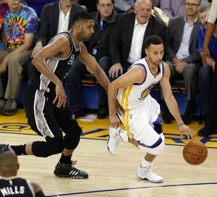 Golden State Warriors' Stephen Curry dribbles past San Antonio Spurs' Tim Duncan in 1st quarter during NBA game at Oracle Arena in Oakland, Calif., on Thursday, April 7, 2016. Photo: Scott Strazzante, The Chronicle