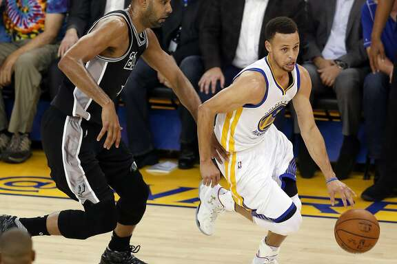 Golden State Warriors' Stephen Curry dribbles past San Antonio Spurs' Tim Duncan in 1st quarter during NBA game at Oracle Arena in Oakland, Calif., on Thursday, April 7, 2016.