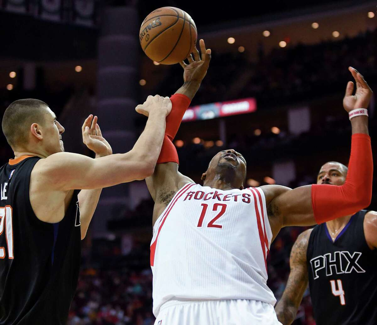 Houston Rockets center Dwight Howard (12) vies for a rebound with Phoenix Suns center Alex Len, left, during the second half of an NBA basketball game, Thursday, April 7, 2016, in Houston. Phoenix won 124-115. (AP Photo/Eric Christian Smith) ORG XMIT: TXES113