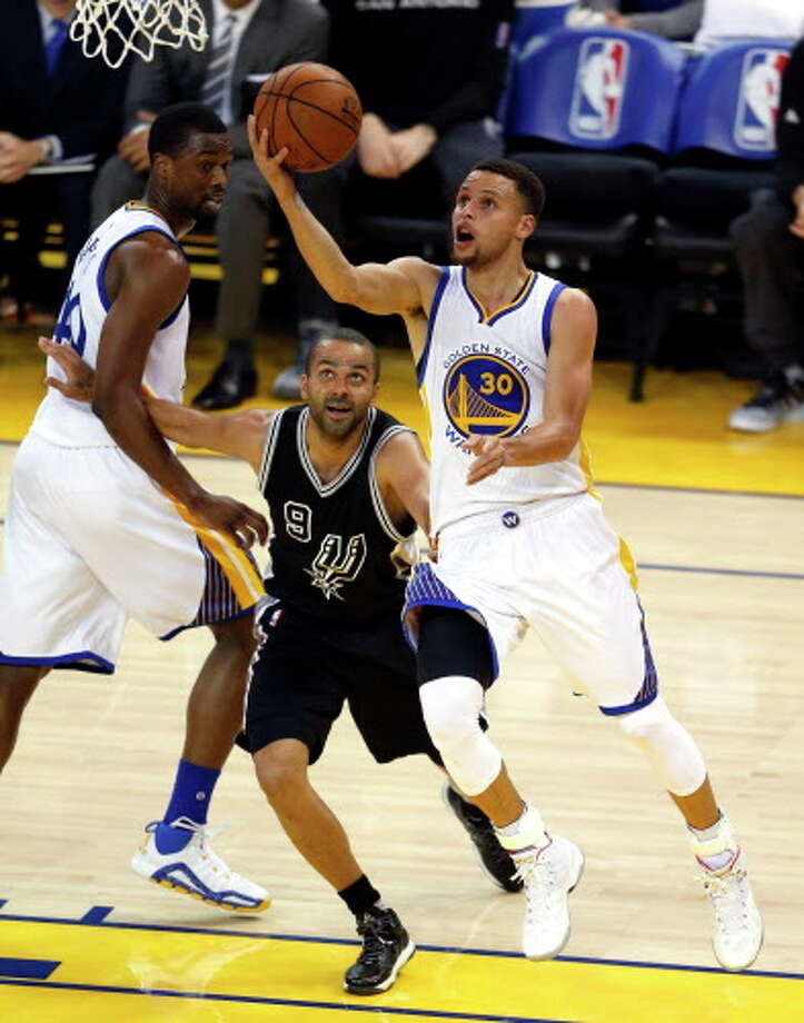 Golden State Warriors' Stephen Curry scores against San Antonio Spurs' Tony Parker in 1st quarter during NBA game at Oracle Arena in Oakland, Calif., on Thursday, April 7, 2016. Photo: Scott Strazzante, AP, Getty / ONLINE_YES