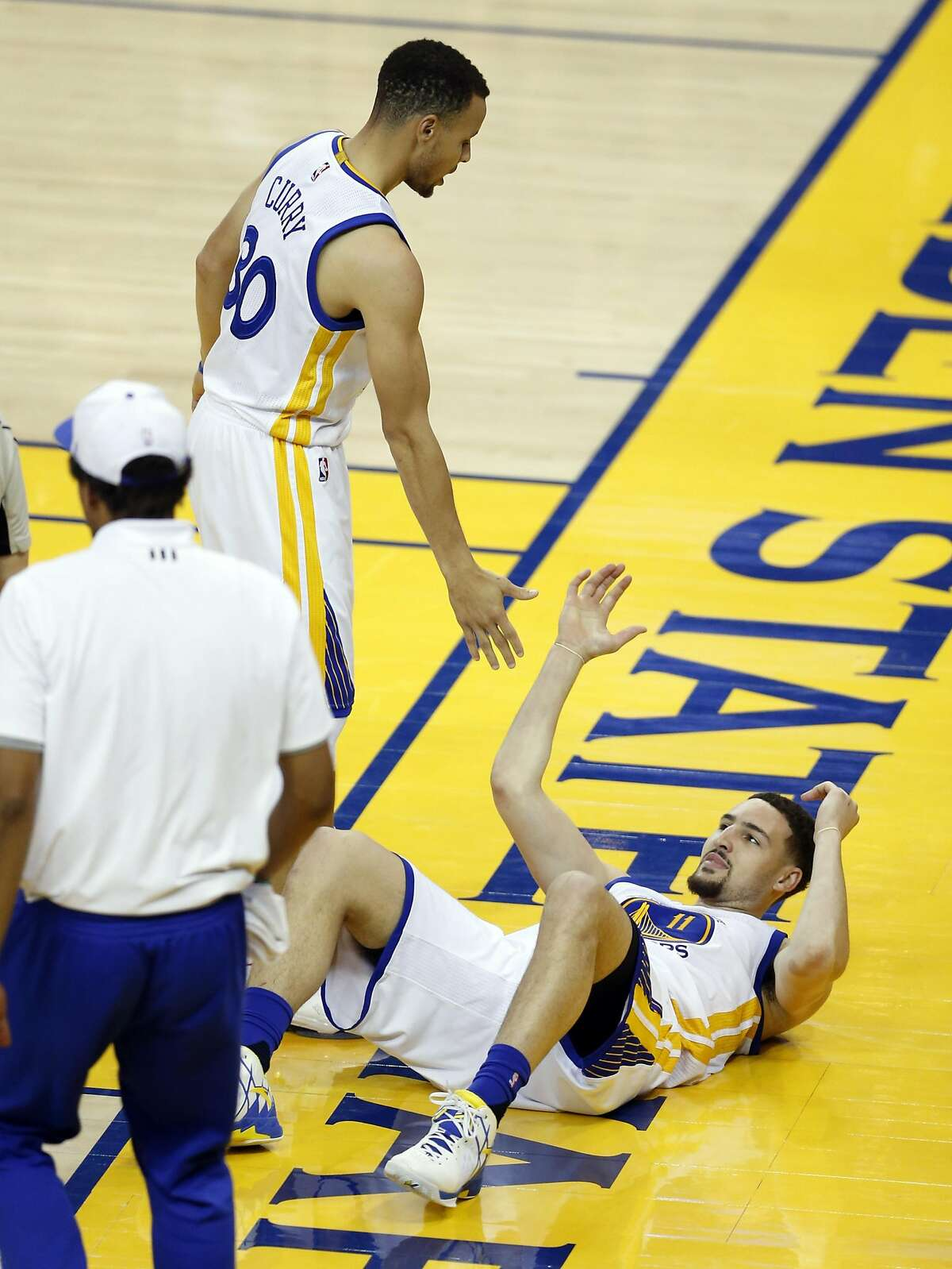 Golden State Warriors' Klay Thompson is helped up by Stephen Curry in 3rd quarter against San Antonio Spurs during NBA game at Oracle Arena in Oakland, Calif., on Thursday, April 7, 2016.