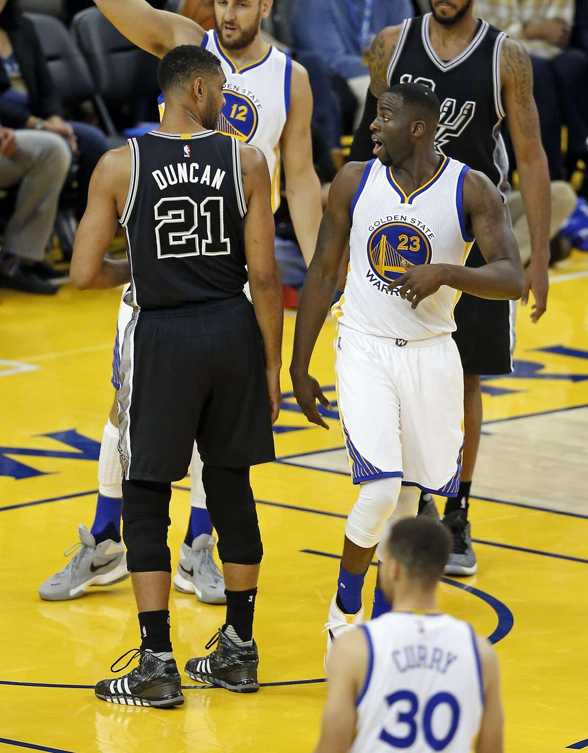 Golden State Warriors' Draymond Green has words with San Antonio Spurs' Tim Duncan in 3rd quarter during NBA game at Oracle Arena in Oakland, Calif., on Thursday, April 7, 2016.