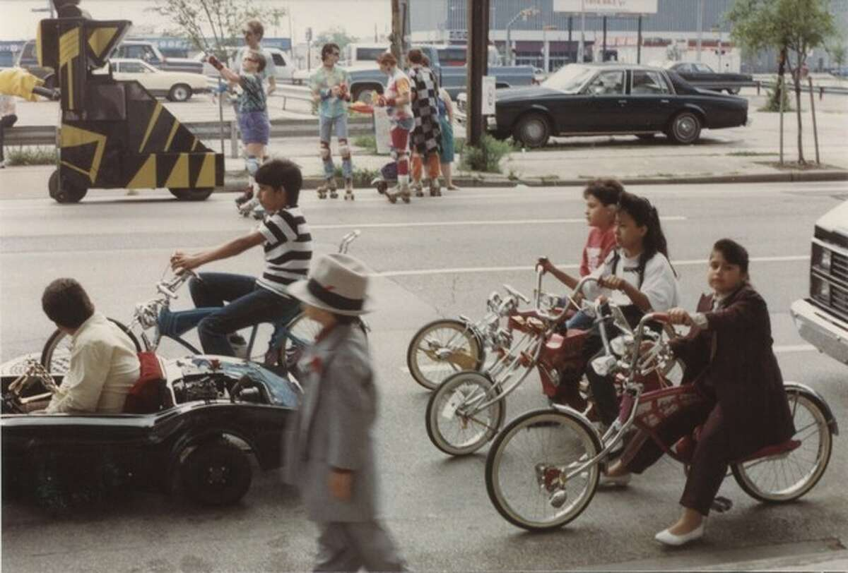 These photos show the scene at the first annual Houston Art Car Parade in 1988 as it rolled through downtown Houston. That first year there were only 40 or so decorated vehicles in the mix. Over 30 years later there are almost 300 cars in the parade and over 250,000 people come out to watch the spectacle.