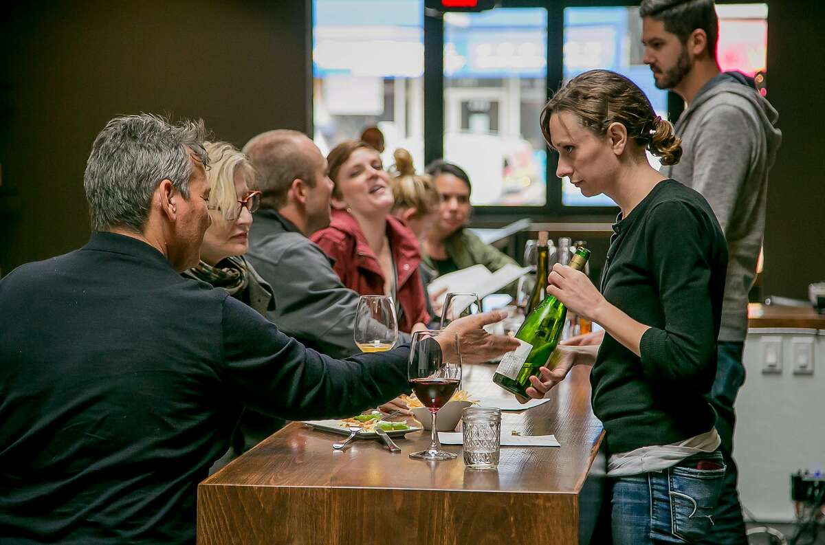Nichole Ream shows a bottle of wine to a customer at the High Treason wine bar in San Francisco, Calif., on April 7th, 2016.