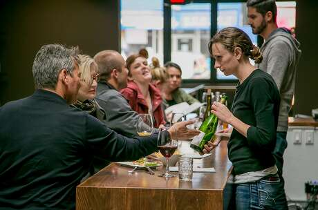 Nichole Ream shows a bottle of wine to a customer at the High Treason wine bar in San Francisco, Calif., on April 7th, 2016. Photo: John Storey, Special To The Chronicle