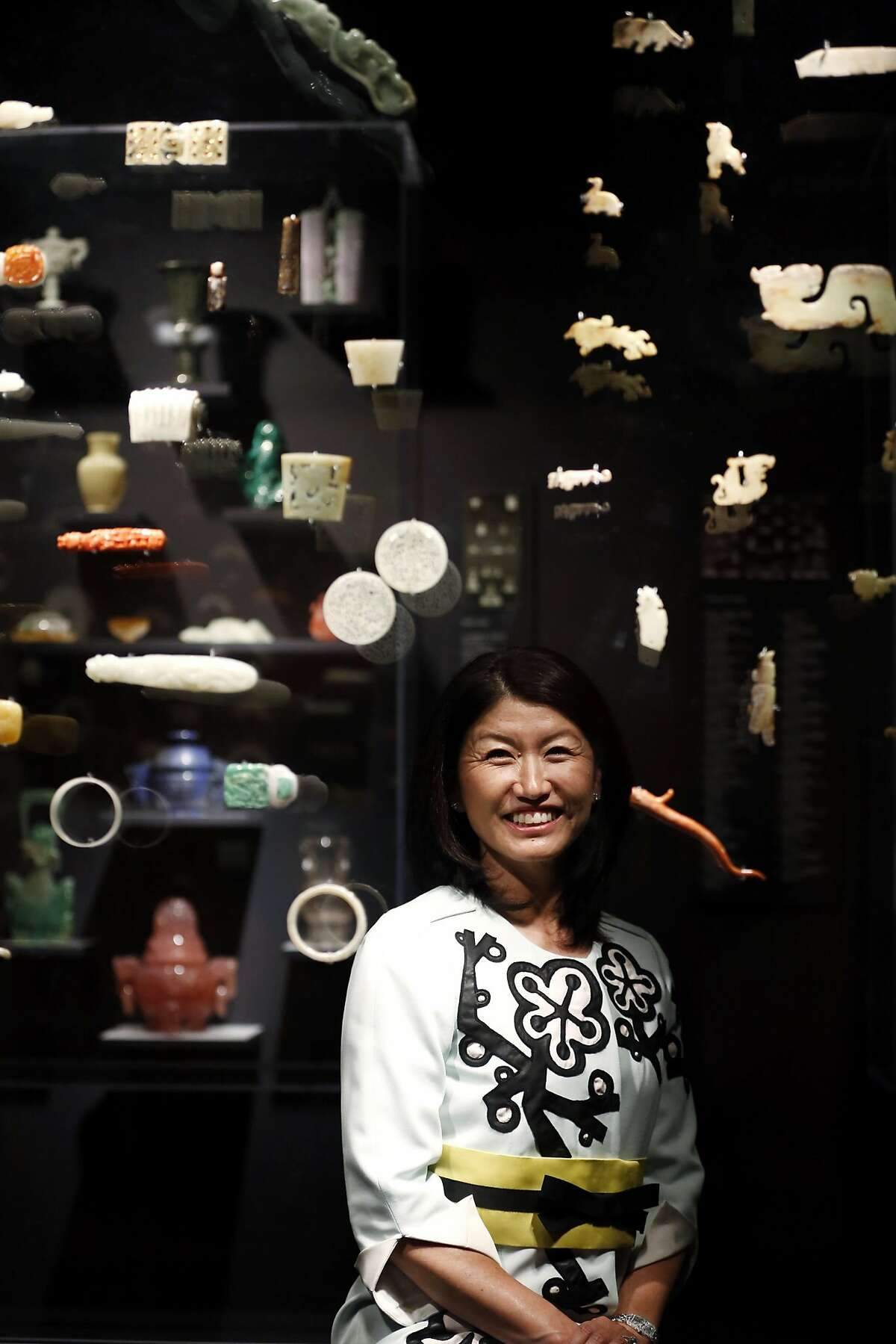 Akiko Yamazaki, chairwoman of the board of the Asian Art Museum, poses for a photograph through a display case filled with jade pieces in the Asian Art Museum in San Francisco, California, on Thursday, April 7, 2016.