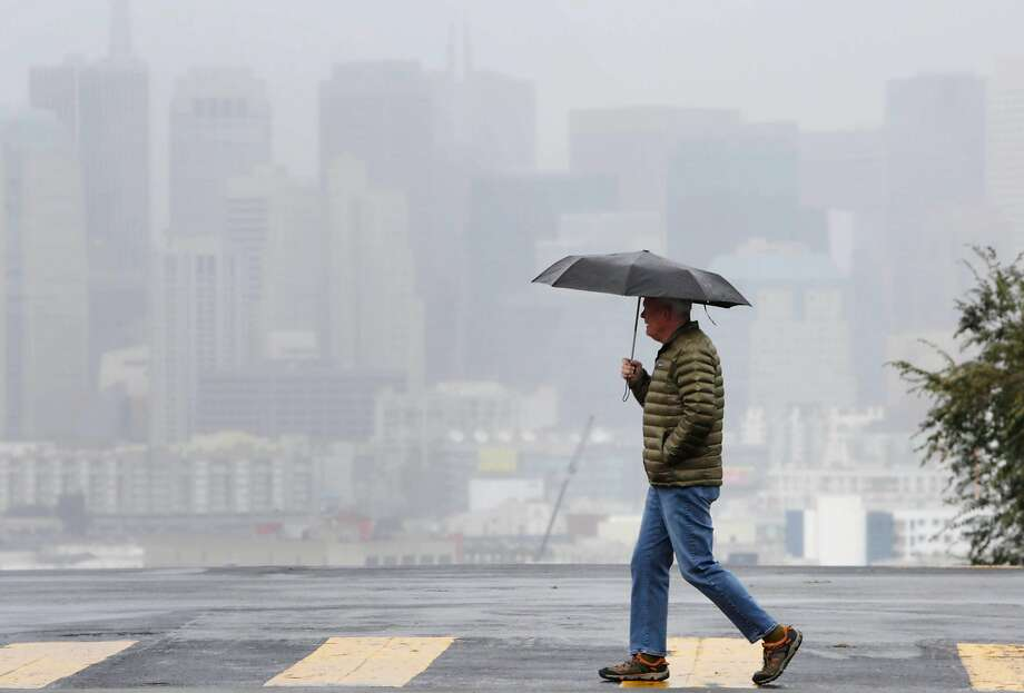 David, San Francisco resident, keeps dry in the rain under an umbrella while crossing Texas Street against a San Francisco skyline obscured by rain on Monday, January 4, 2015 in San Francisco, Calif. Photo: Lea Suzuki, The Chronicle