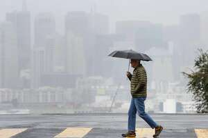 David, San Francisco resident, keeps dry in the rain under an umbrella while crossing Texas Street against a San Francisco skyline obscured by rain on Monday, January 4, 2015 in San Francisco, Calif.