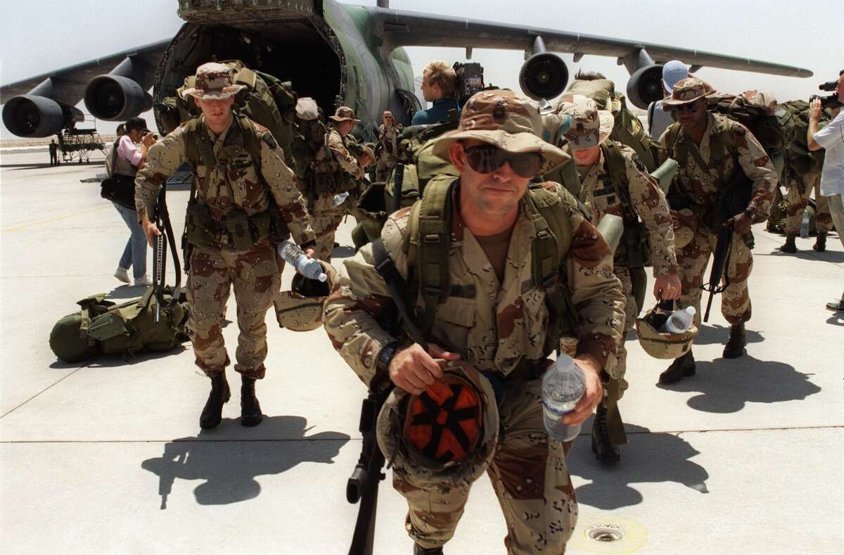 """Aug. 21, 1990: More than 1,000 U.S. Marines from Fort Bragg disembark from a Galaxy transport plane at Saudi Dhahran air base. Iraq's invasion of Kuwait, ostensibly over violations of the Iraqi border, led to the Gulf War which began on Jan. 16, 1991. A U.S.-led multi-national force repulsed Iraq from Kuwait during the """"Desert Storm"""" offensive and a cease-fire was signed on Feb. 21, 1991."""