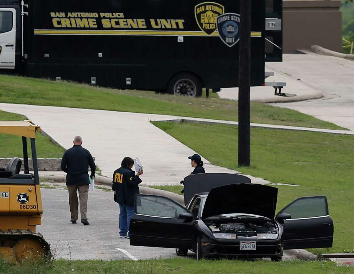 FBI personnel stand near a vehicle located inside Lackland AFB, Medina Annex on Friday, Apr. 8, 2016. Earlier, two men died in an apparent murder-suicide near Forbes Hall within the annex Friday morning that left the base locked down for nearly 2 hours, officials said.