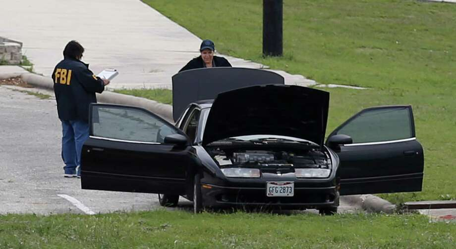 FBI personnel stand near a vehicle located inside Lackland AFB, Medina Annex on Friday, Apr. 8, 2016. Earlier, two men died in an apparent murder-suicide near Forbes Hall within the annex Friday morning that left the base locked down for nearly 2 hours, officials said. Photo: Kin Man Hui, San Antonio Express-News / ©2016 San Antonio Express-News